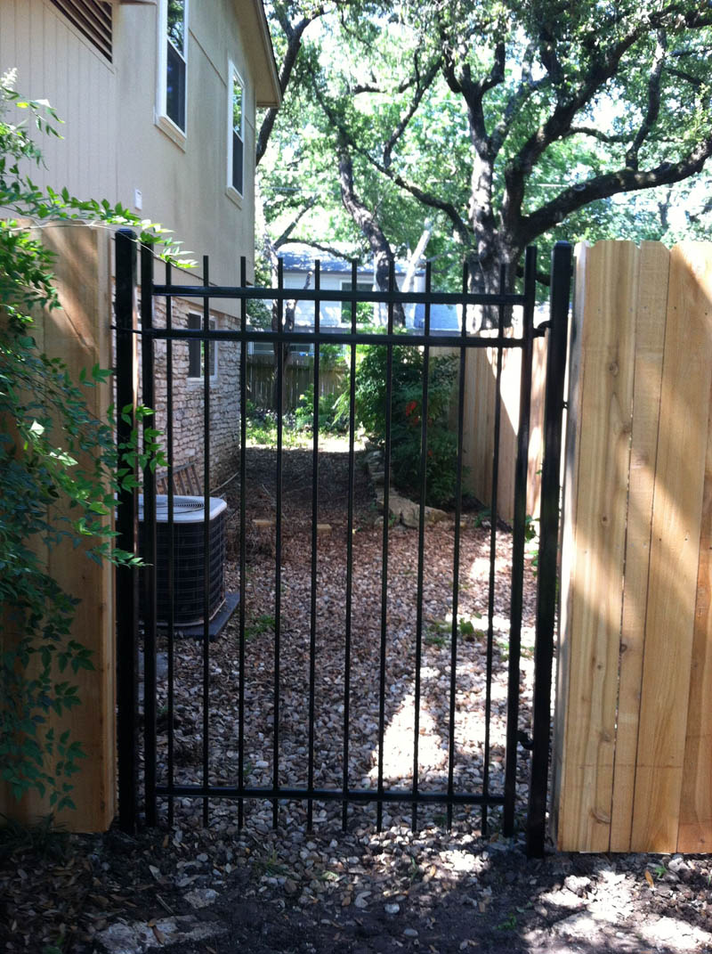 ornamental iron gate at wood fence